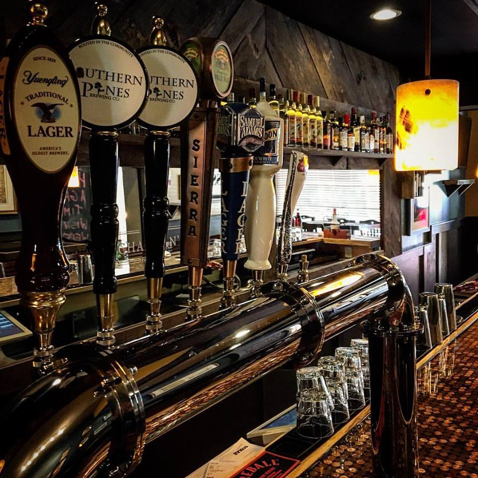 Row of beer taps at bar. Yuengling, Southern Pines, Sierra, Sam Adams, Blue Moon