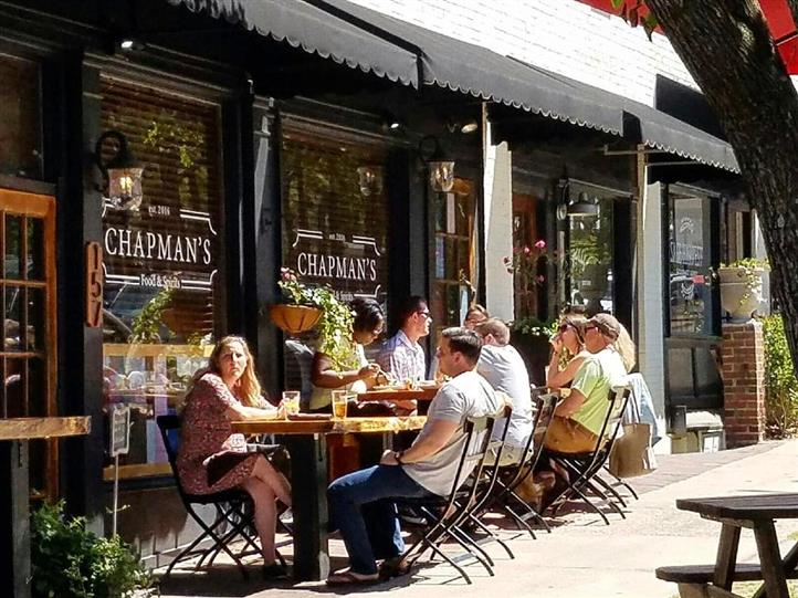 Chapman's Food & Spirits storefront and sidewalk with patrons dining outside