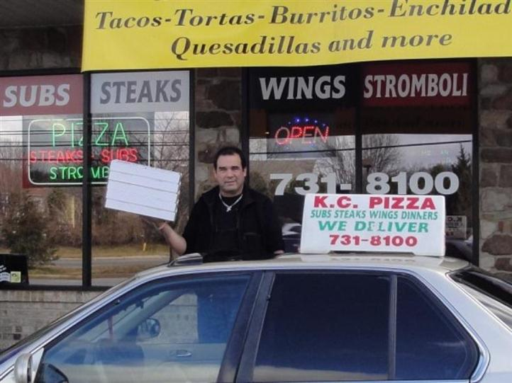 Delivery man holding pizzas next to KC's pizza delivery car