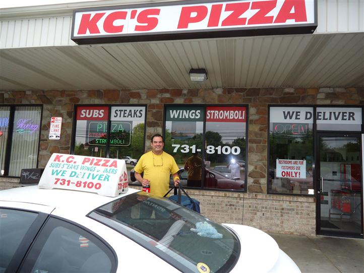KC's Pizza sign over store front entrance with delivery man with KC's Pizza delivery car.