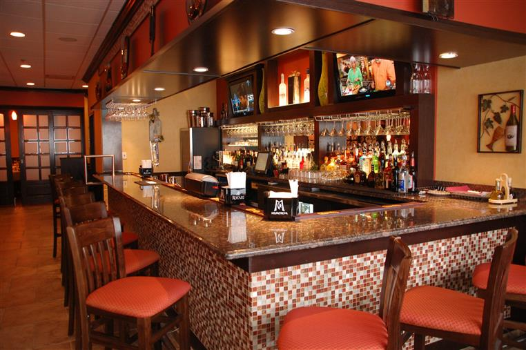 interior bar area with liquor bottles and stools for customers