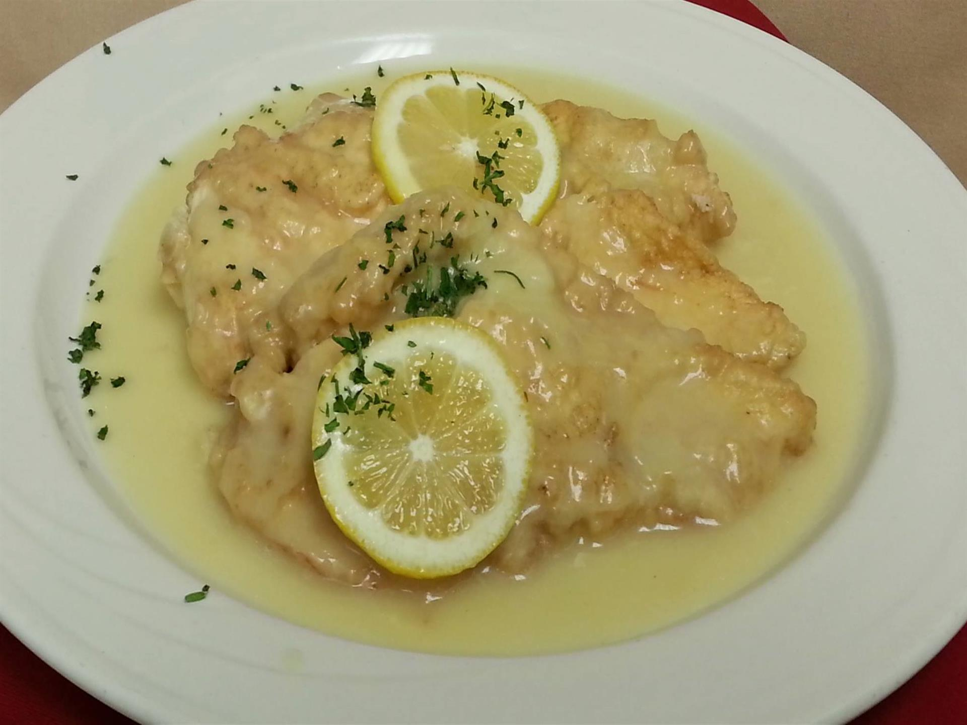 cooked chicken breats with sauce and lemon wedges
