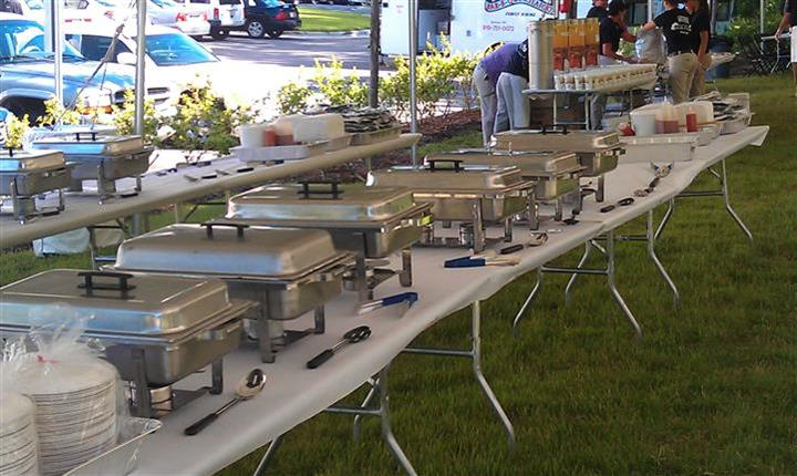 buffet trays on a table under a tent