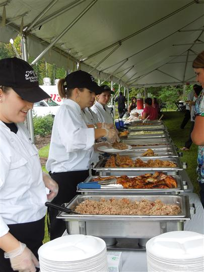 employees serving food in a buffet line