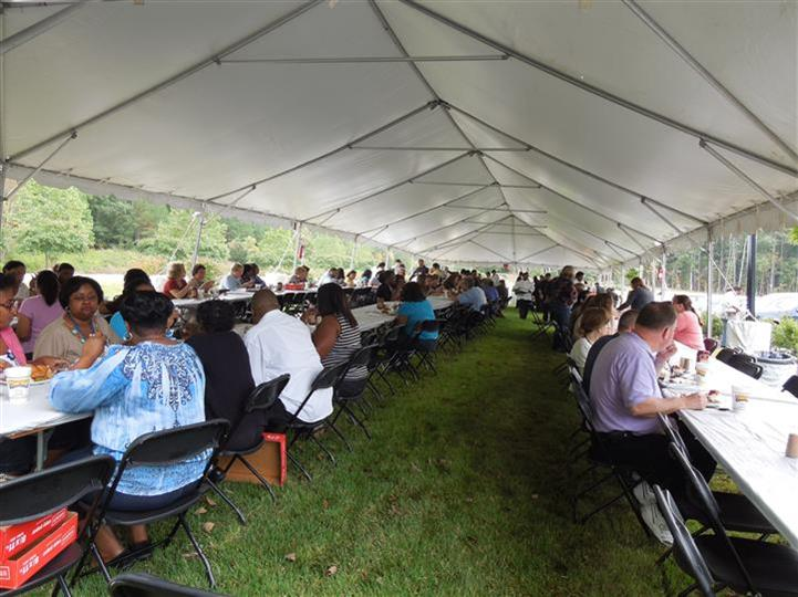 people eating food under a catering tent