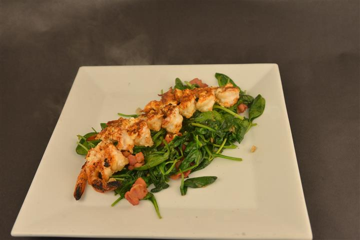 Shrimp topped on leafy greens