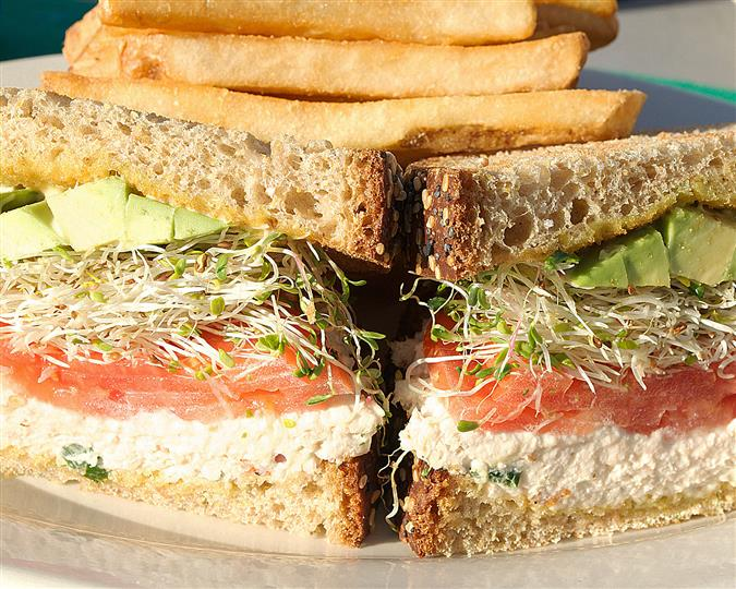 Cali club sandwich with chicken salad, tomato, avocado and beansprouts on rye bread served with french fries