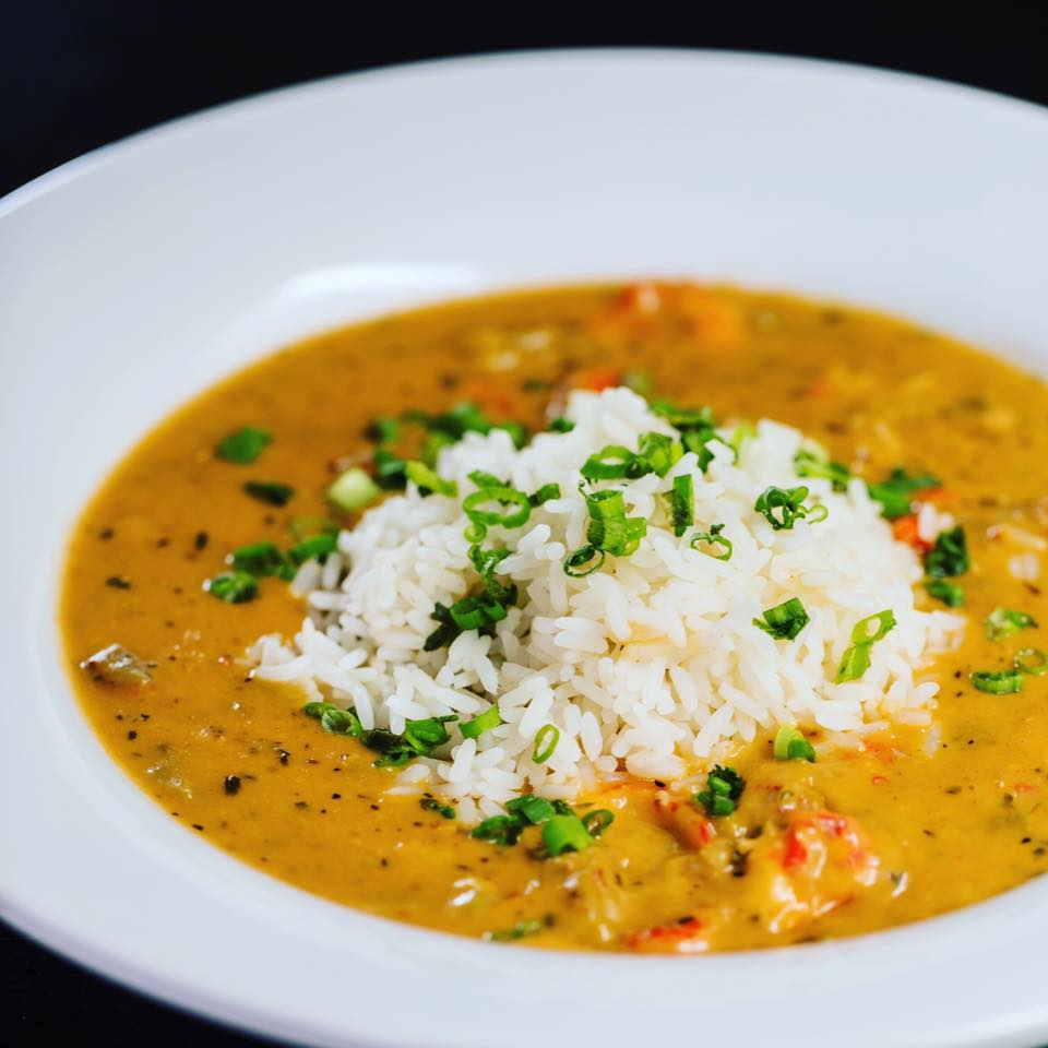 creamy soup topped with rice and scallions
