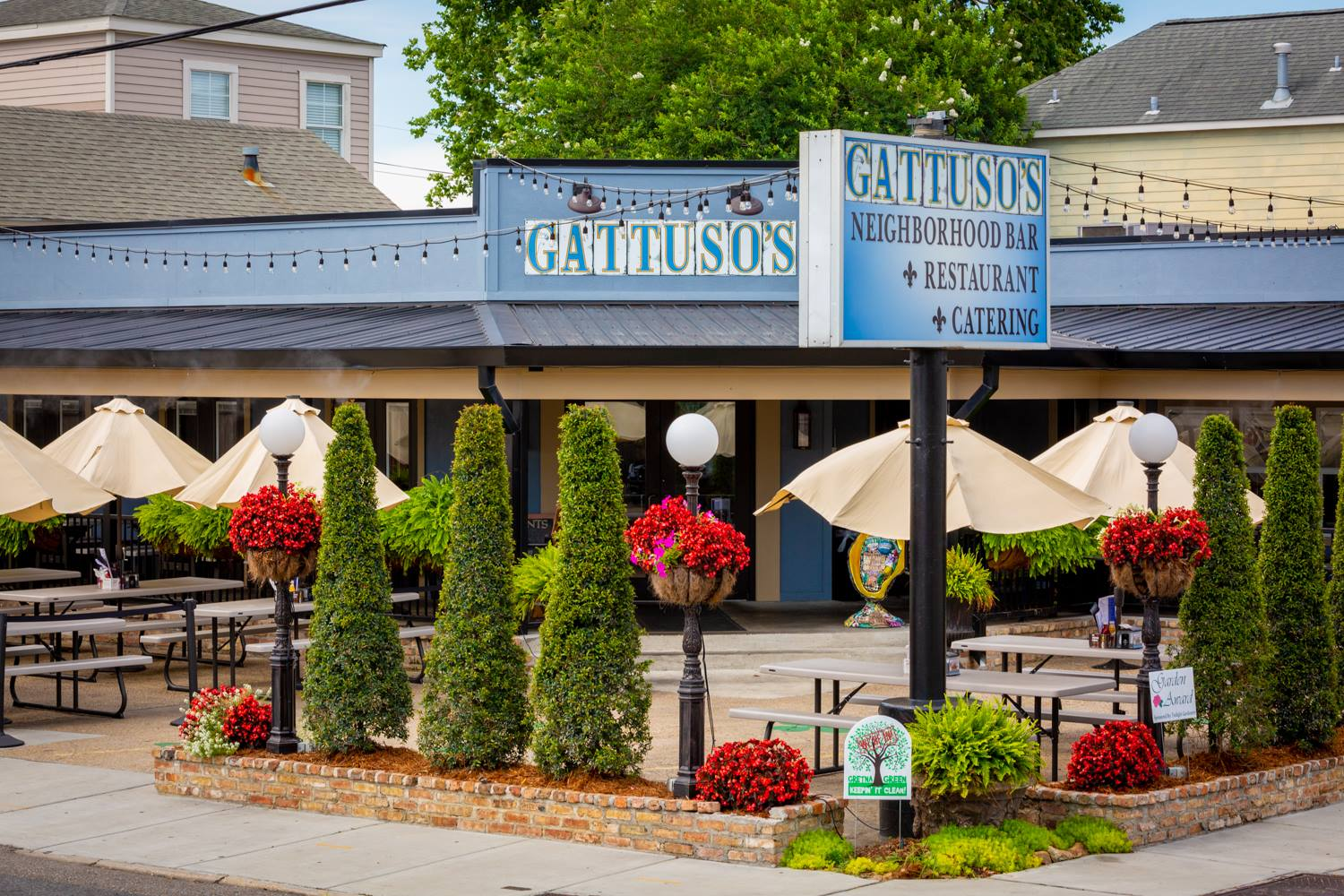 Outdoor shot of Gattusos restaurant with lots of plants and greenery and outdoor tables set up with umbrellas