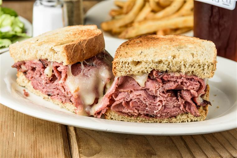 corned beef sandwich served on toasted rye bread with a side of fries