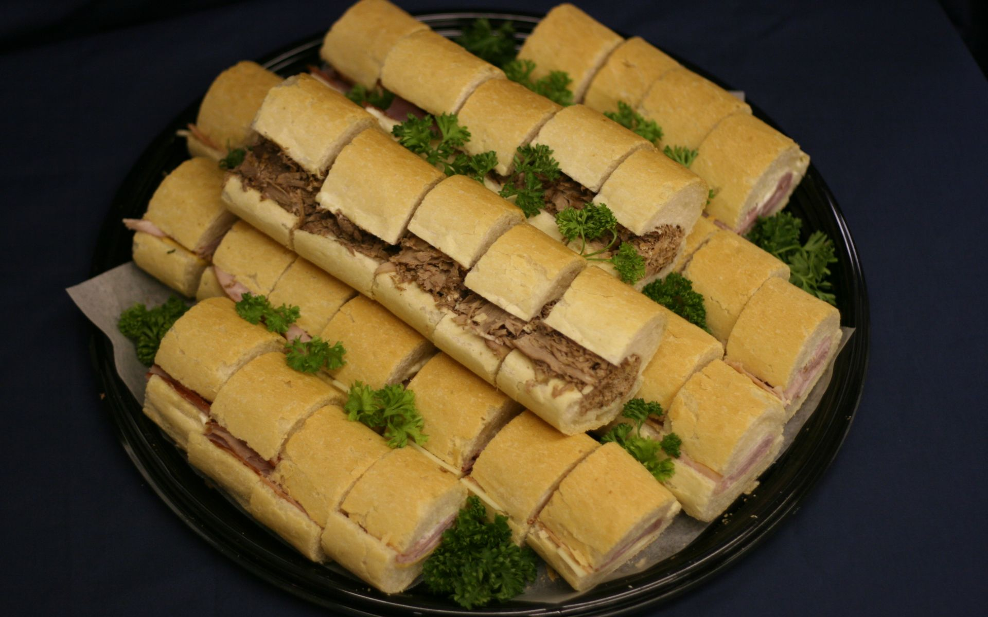 Sliced sandwiches stacked on a plastic tray