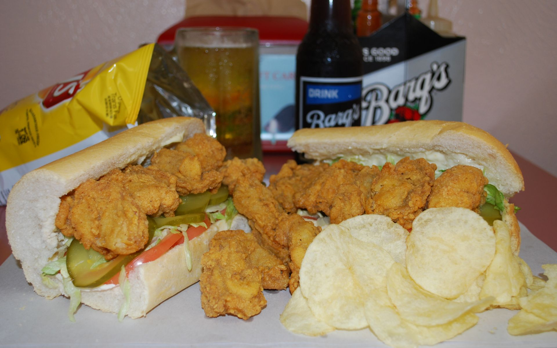 Fried shrimp poboy with lettuce, tomato and pickles and a side of potato chips