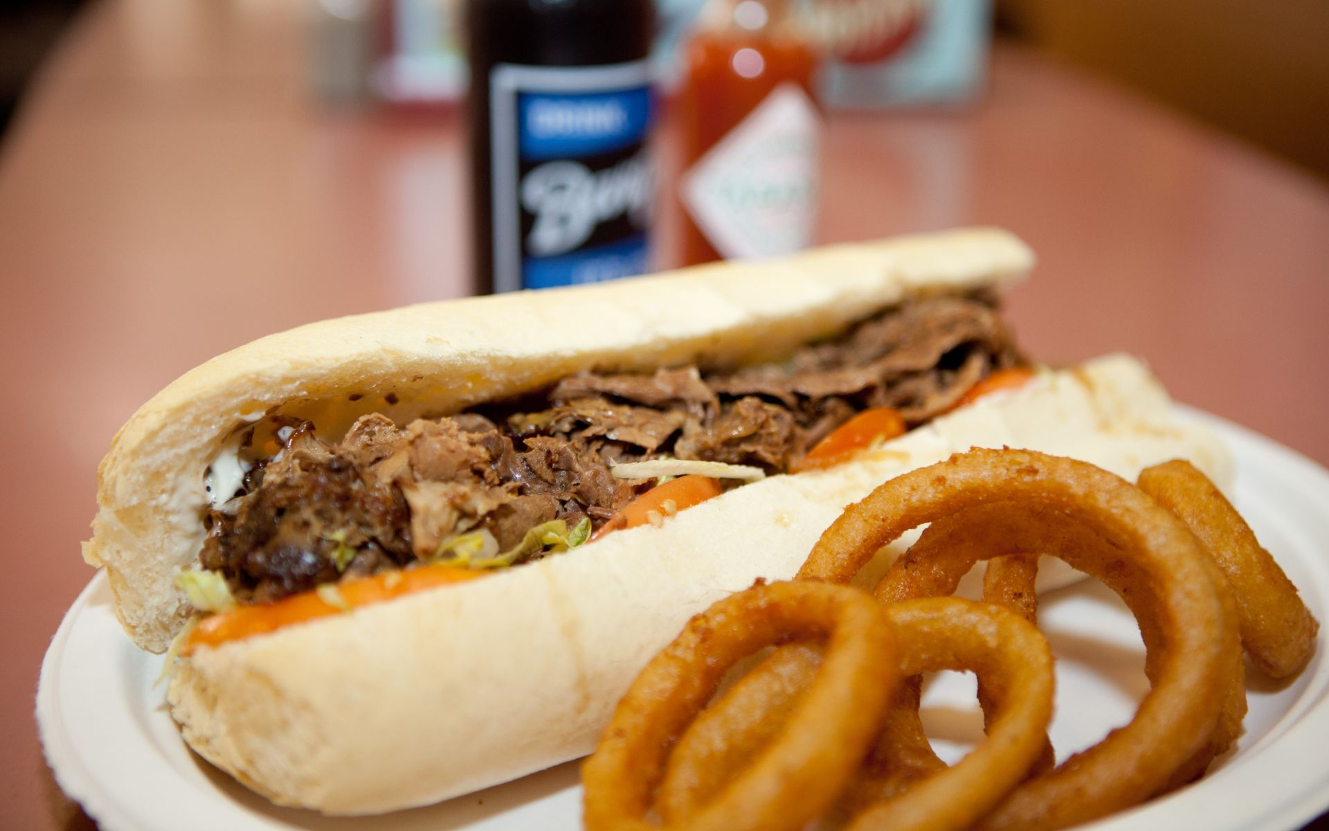 Pulled pork poboy with lettuce and tomato with onion rings