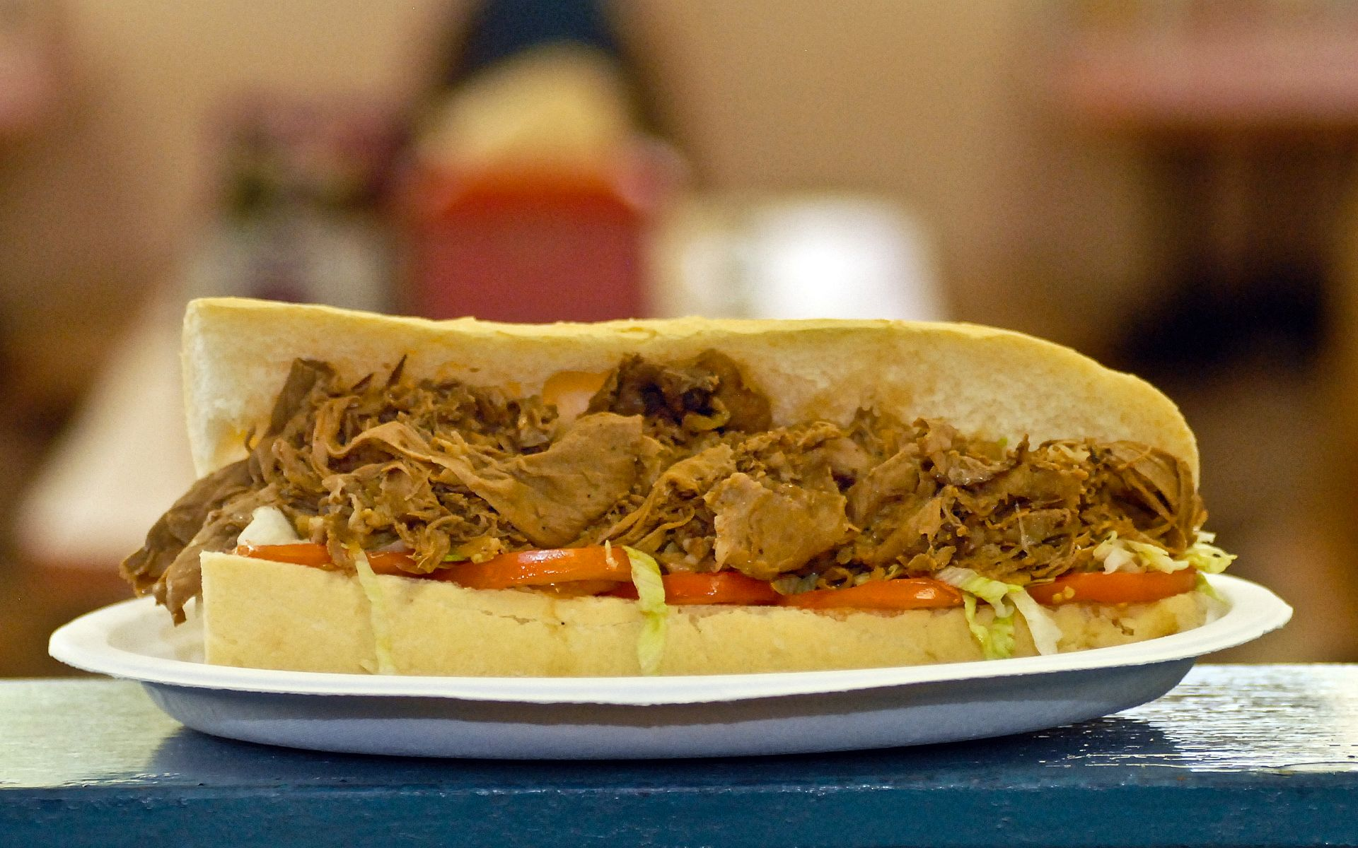 Pulled pork poboy with lettuce and tomato served on a white plate on top of the counter