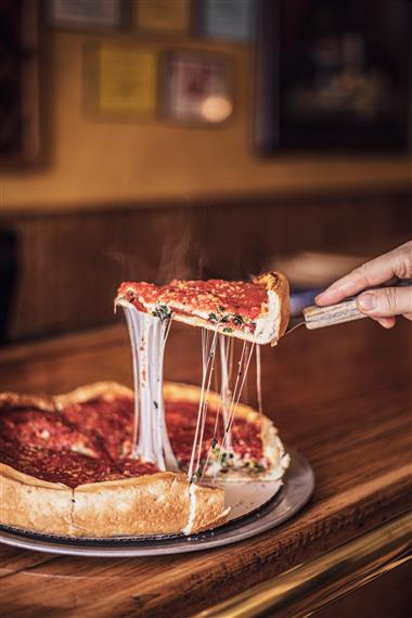 someone taking a slice out of a Chicago deep dish style pizza