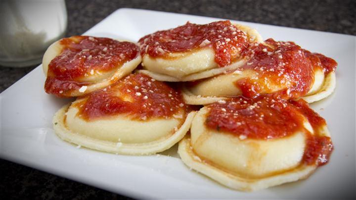 Raviolis with red sauce on white plate
