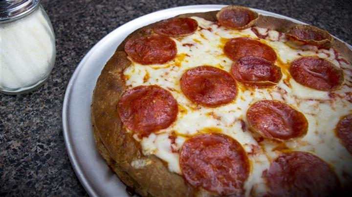 pepperoni pizza on white plate next to salt shaker