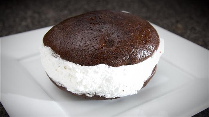 Chocolate whoopie pie with cream filling on white plate