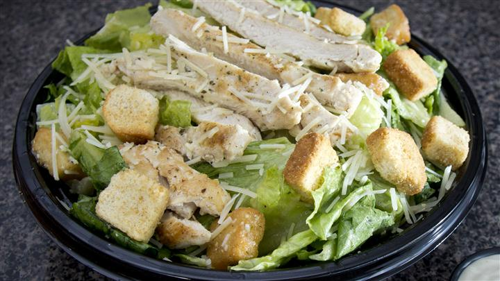 Chicken cesar salad with shredded chicken, cheese, and croutons