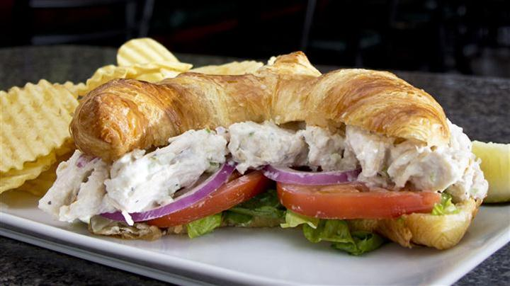 Chicken Salad on a croissant with onions tomato and lettuce with chips and pickles as sides