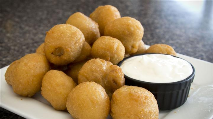 Hush puppies on white plate with white dipping sauce