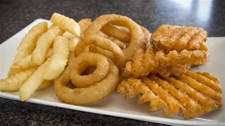 onion rings, french fries, and waffle fries on white plate