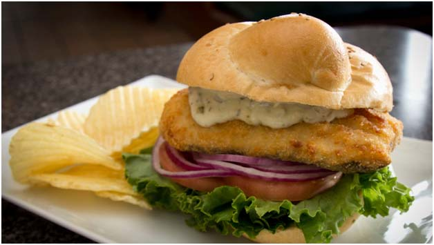 Fish sandwich with tarter sauce, onions, lettuce, and tomatoes with side of chips