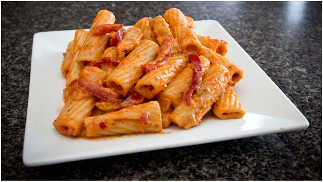 Rigatoni pasta with red sauce on white plate