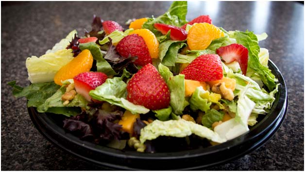 Salad with strawberries and oranges in black bowl