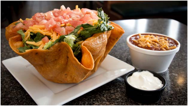 Taco Salad with tortilla bowl with side of chili and sour cream