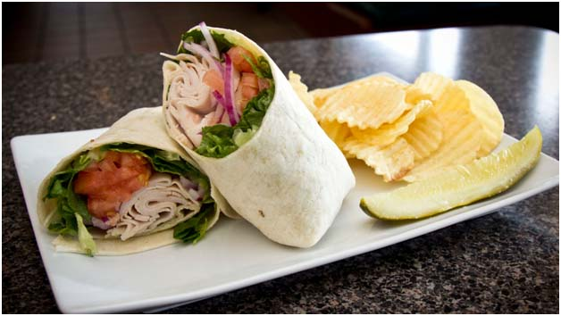 Turkey wrap with lettuce, tomatoes, and onions with side of chips and a pickle