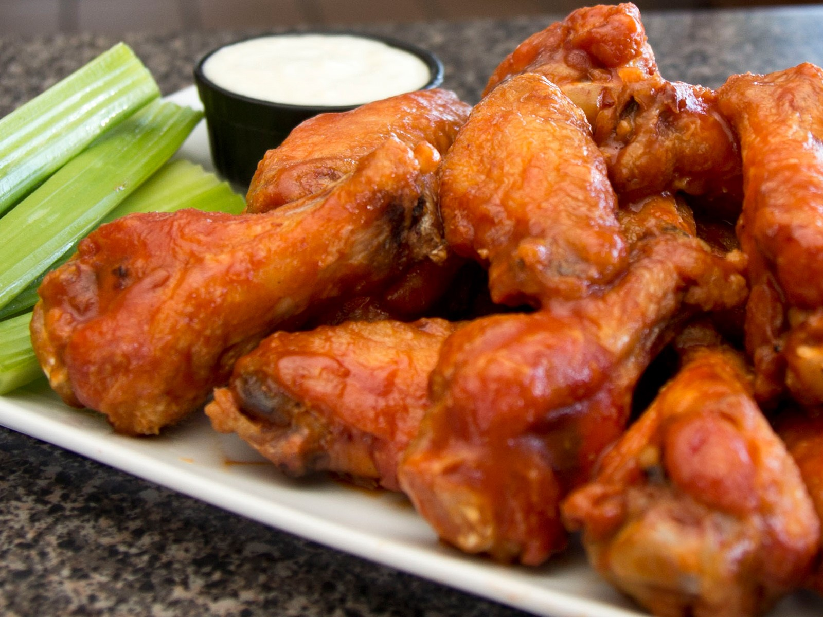 Chicken wings covered in buffalo sauce next to celary and blue cheese