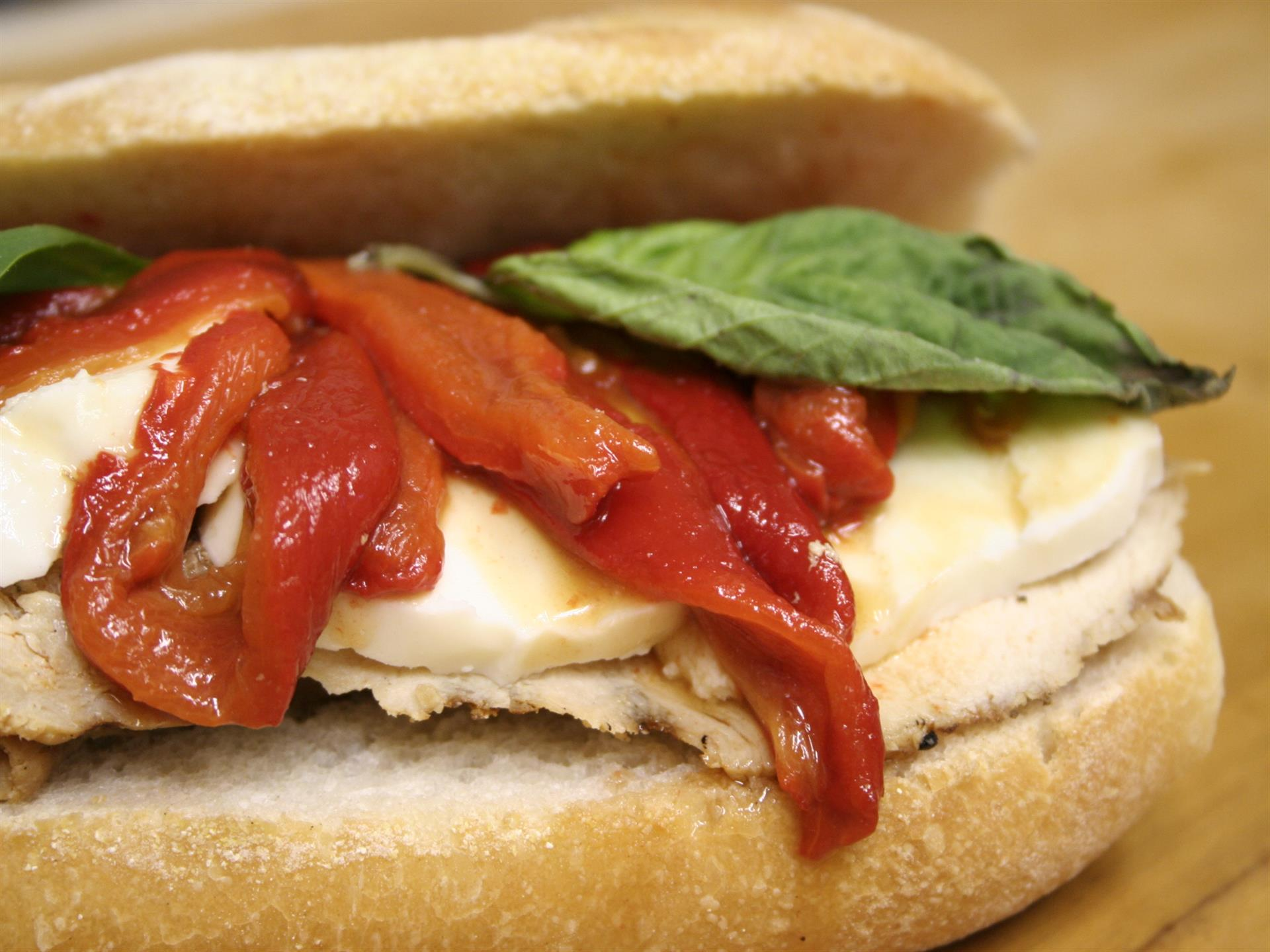 Sandwich with red peppers, chicken, and basil