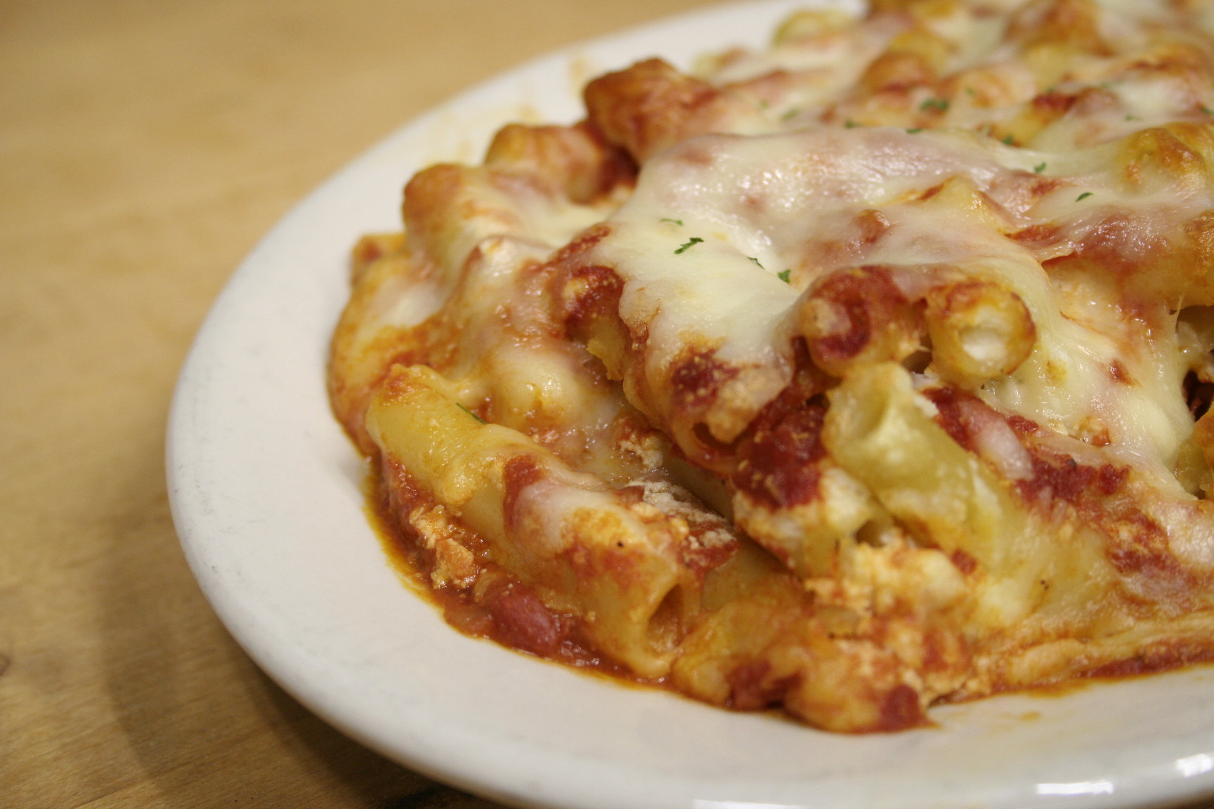 Baked ziti topped with red sauce and melted mozzarella