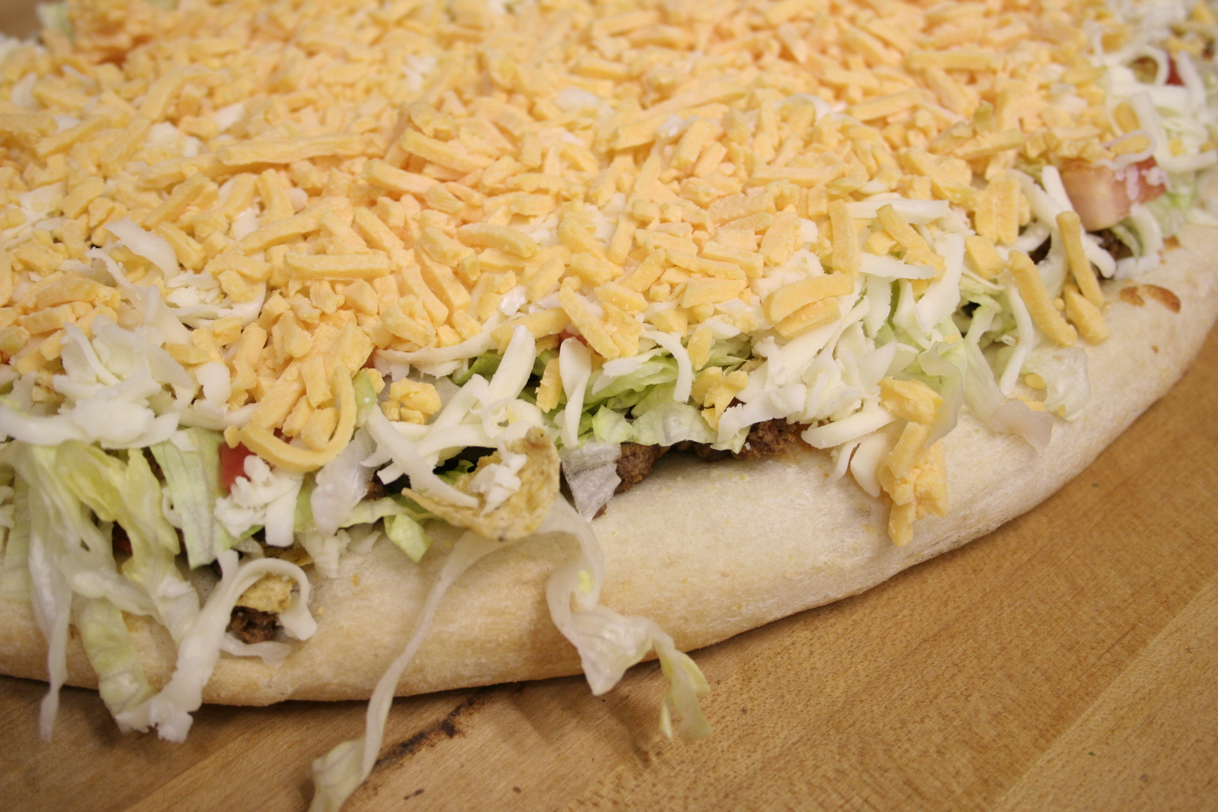 Pizza with lettuce and shredded cheddar cheese on wooden table