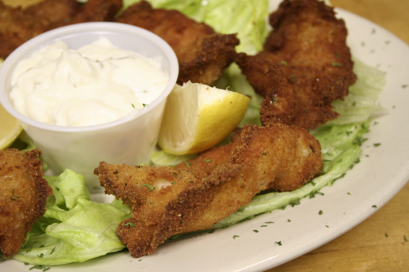 Fried appetizer on bed of lettuce with white dipping sauce