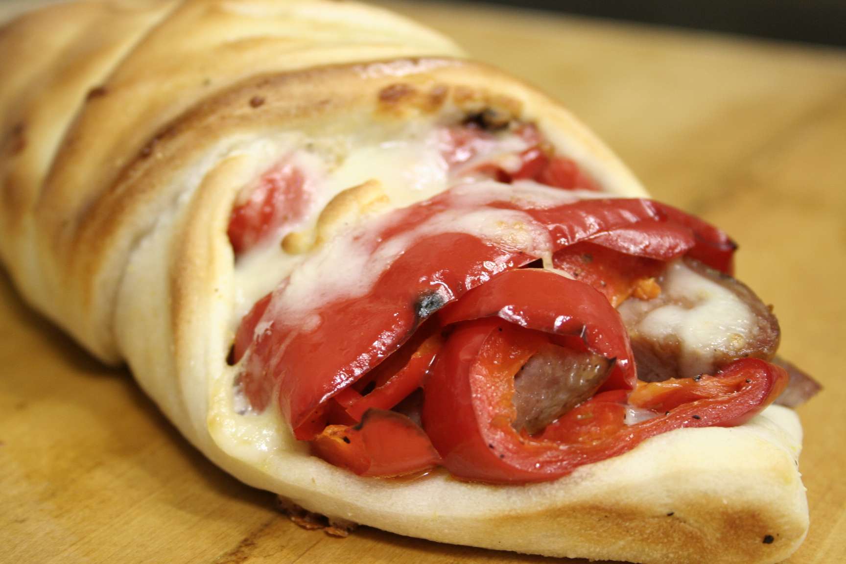 Stromboli with peppers, sausage, and cheese on wood table