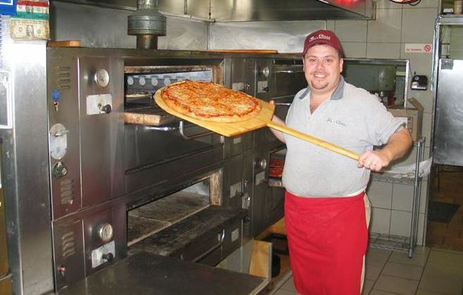 Man holding cheese pizza on a pizza paddle infront of an oven