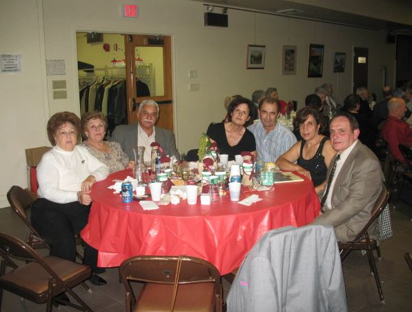 Family at table with red table cloth posing for a picture