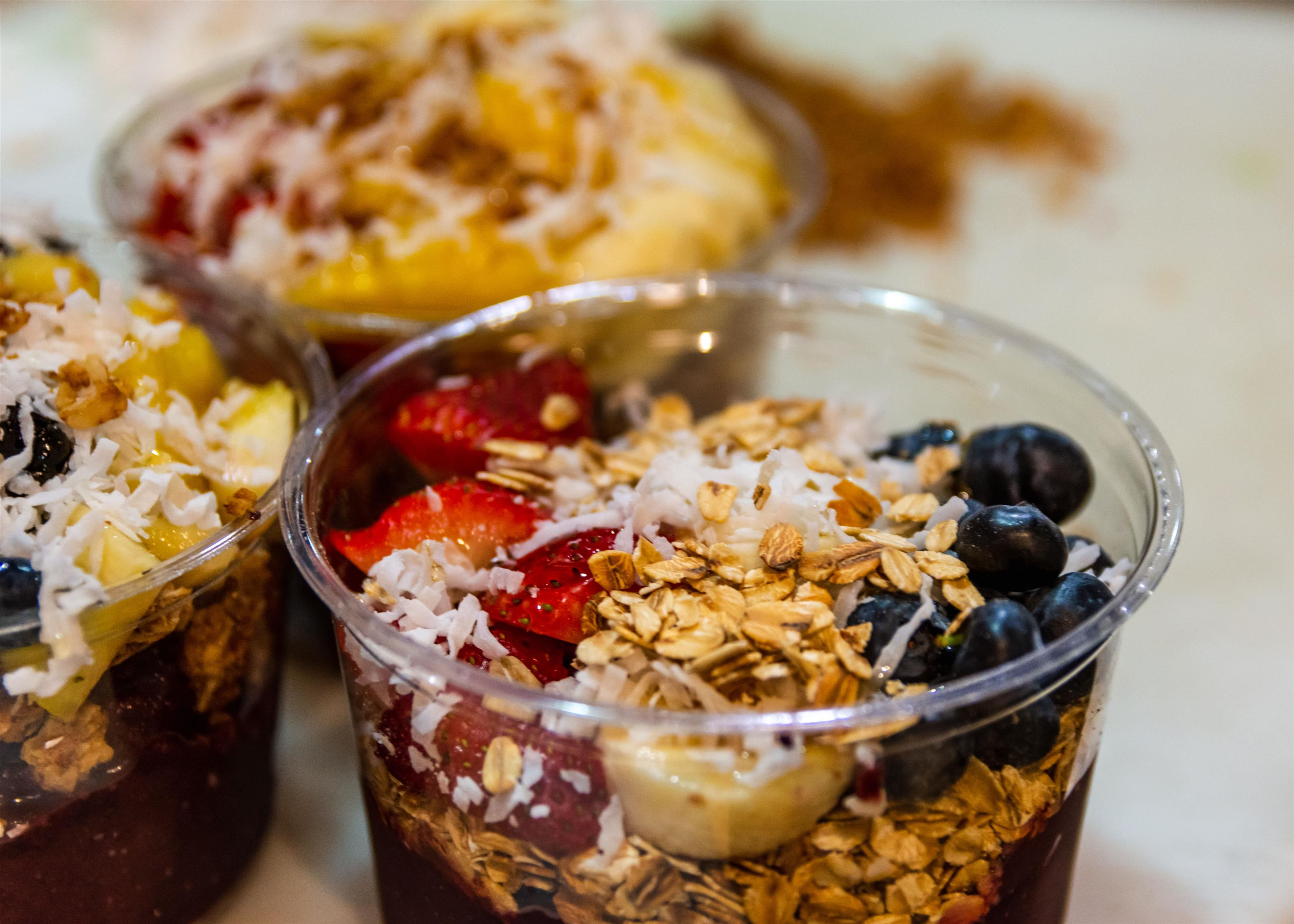 various fruit topped with granola in a cup
