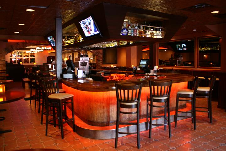 photo of the bar with alcohol stored underneath, televisions, and bar stools around