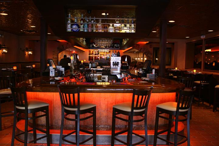 photo of the bar with bottles of liquor lined up above the bar and bar stools around it
