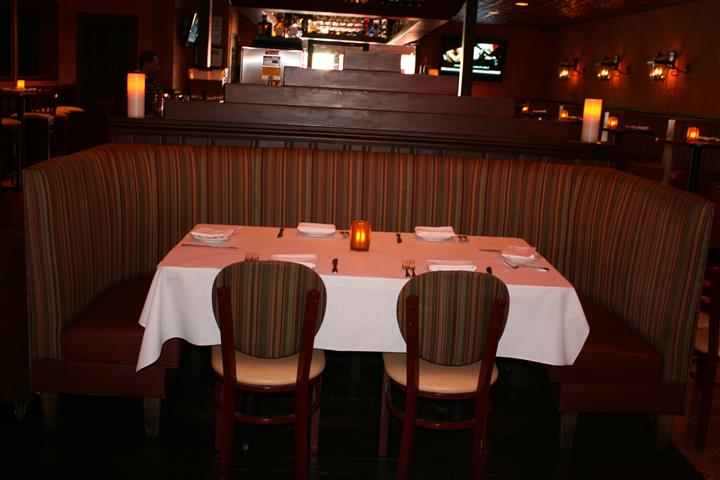 white tablecloth table with a candle in the middle, in a booth with chairs around