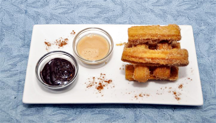 churros with two sides of different sauces to dip