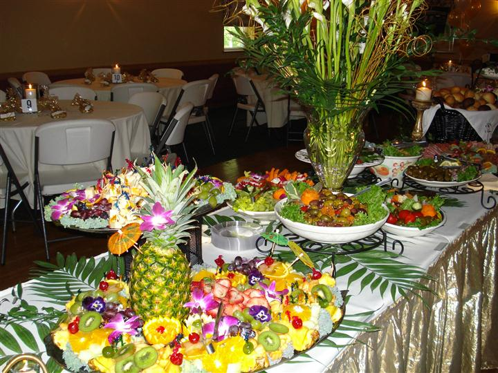 A table set with a fruit platter, olives and other food