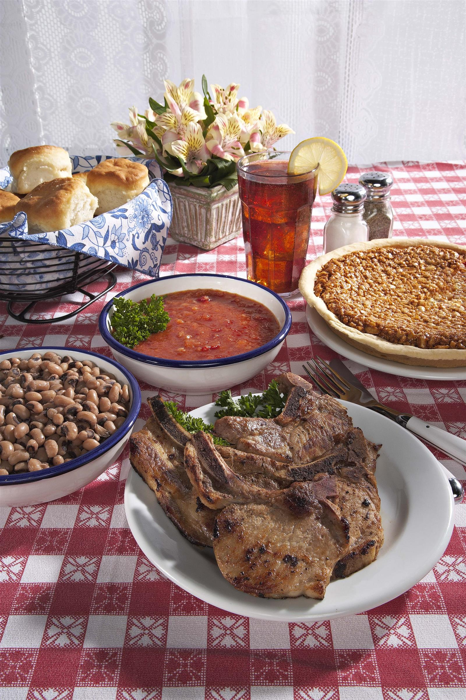 A table filled with different meals, such as soup, pork, biscuits, and a pie.