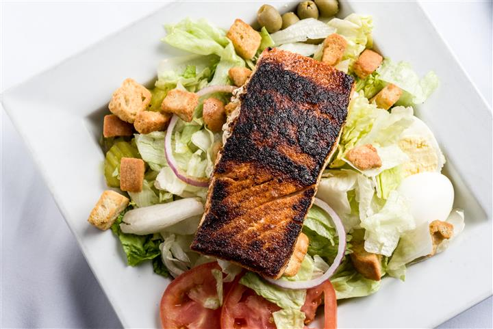 salad with croutons, tomato, red onion topped with salmon