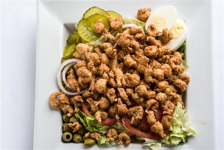lettuce, tomato, olives, pickle slies, hard boiled eggs and breaded bite size chicken