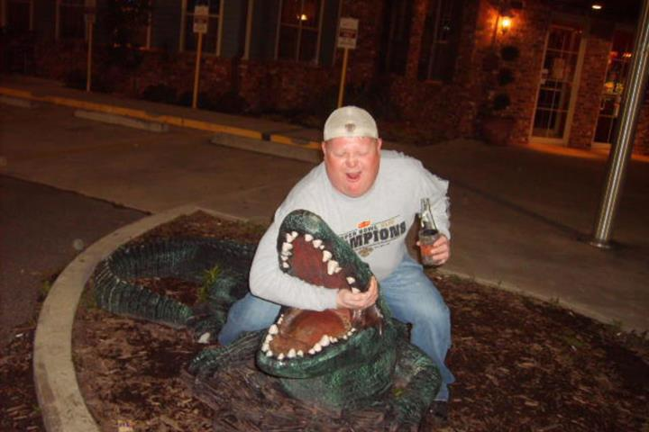 man  posing with fake alligator