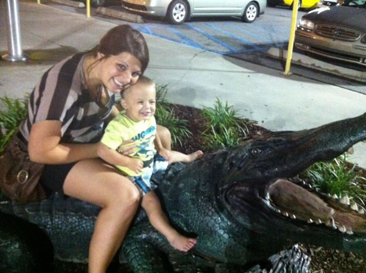woman and little boy posing with fake alligator